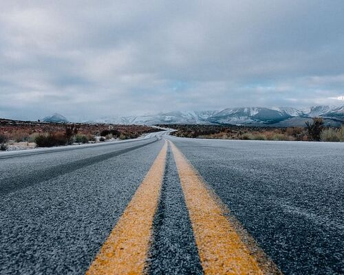 landscape-photography-of-asphalt-road-under-cloudy-sky-during-daytime